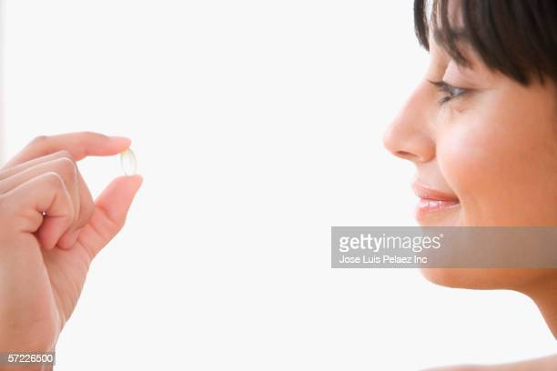 Profile of woman holding vitamin between fingers
