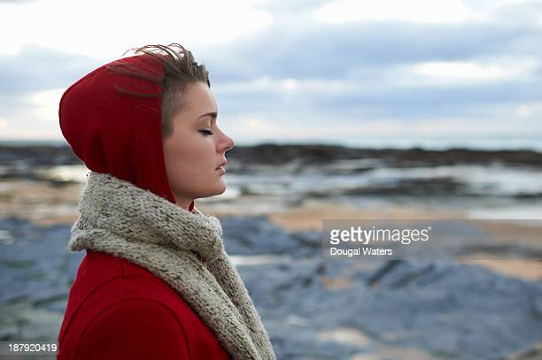 Profile of woman in red coat on coastline.