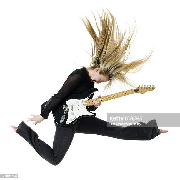 Profile of woman jumping with electric guitar