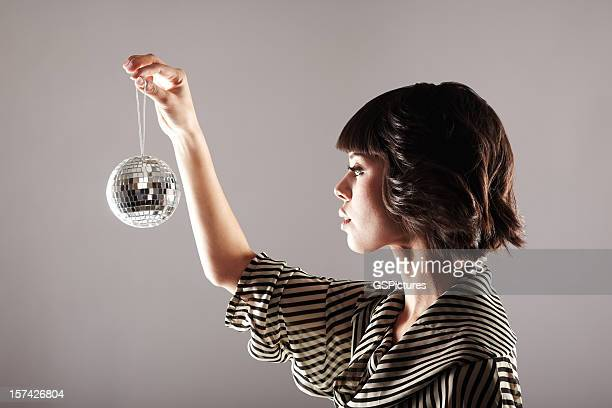 Profile of woman looking at small disco ball