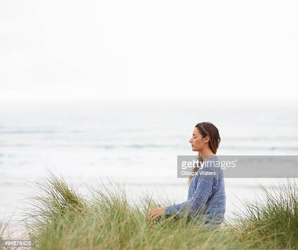 Profile of woman meditating at beach.