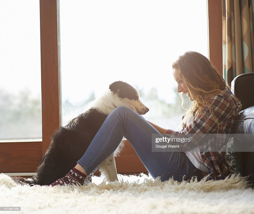 Profile of woman sitting in lounge with dog. : Stock Photo