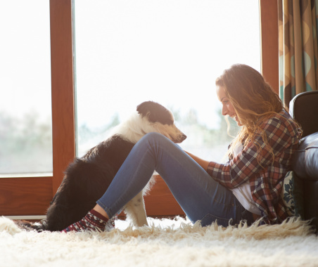 Profile of woman sitting in lounge with dog.