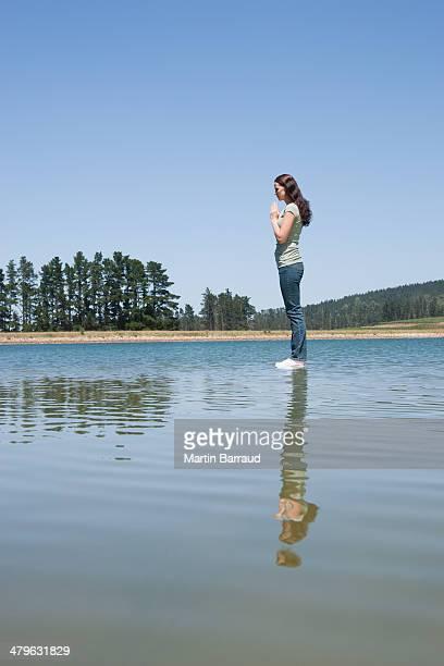 Profile of woman standing on water praying