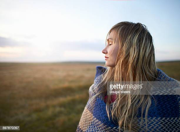Profile of woman with eyes closed in countryside.