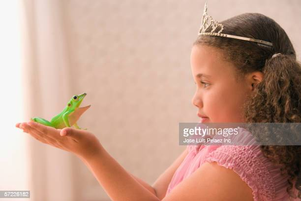 Profile of young girl wearing crown and holding frog