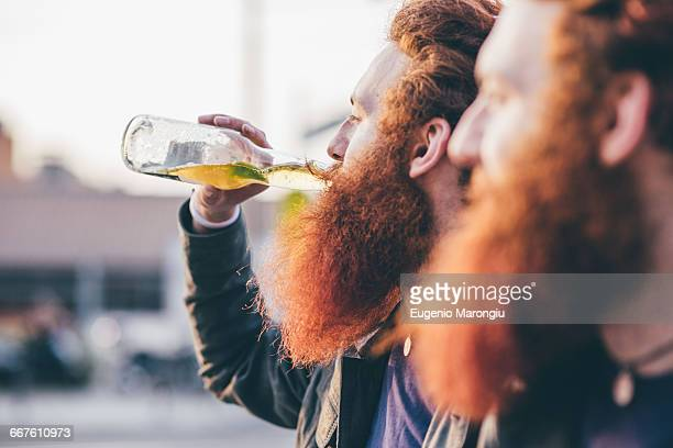 Profile of young male hipster twins with red hair and beards drinking bottled beer