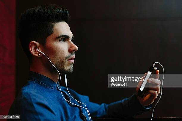 Profile of young man hearing music with earphones in front of black background
