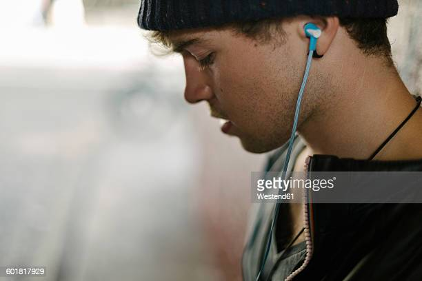 Profile of young man hearing music with earphones