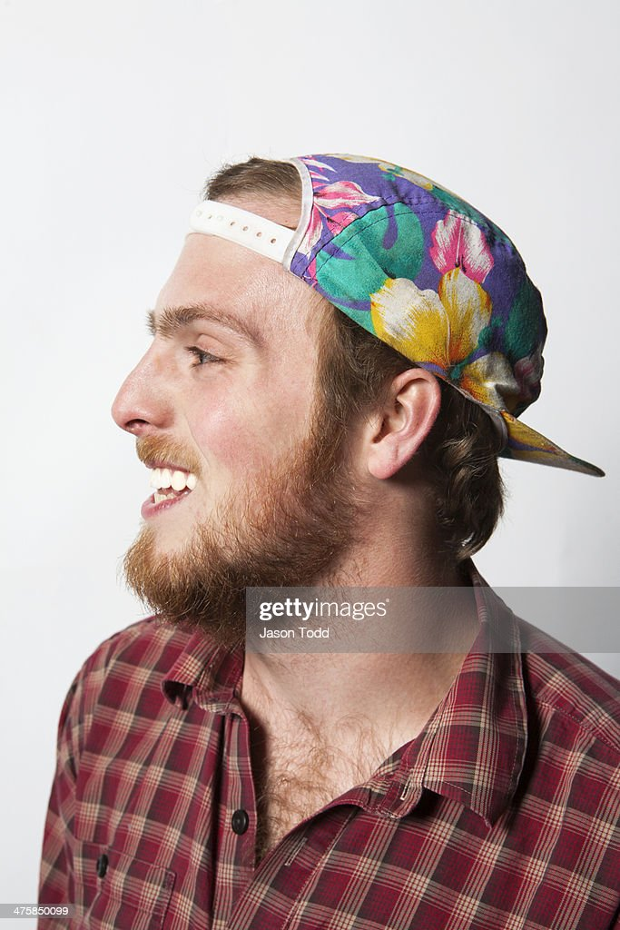 profile of young man smiling with floral hat
