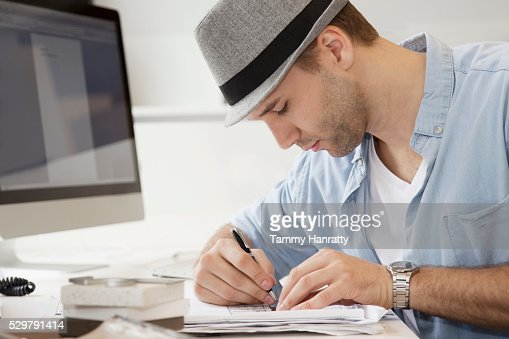 Profile of young man writing at desk : Stock Photo