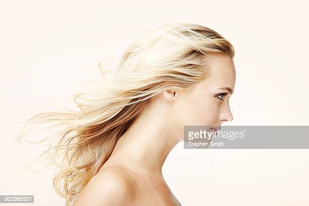 Profile of young woman hair blowing in wind