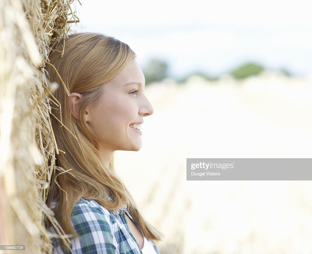 Profile of young woman leaning against hay bail. : Stock Photo