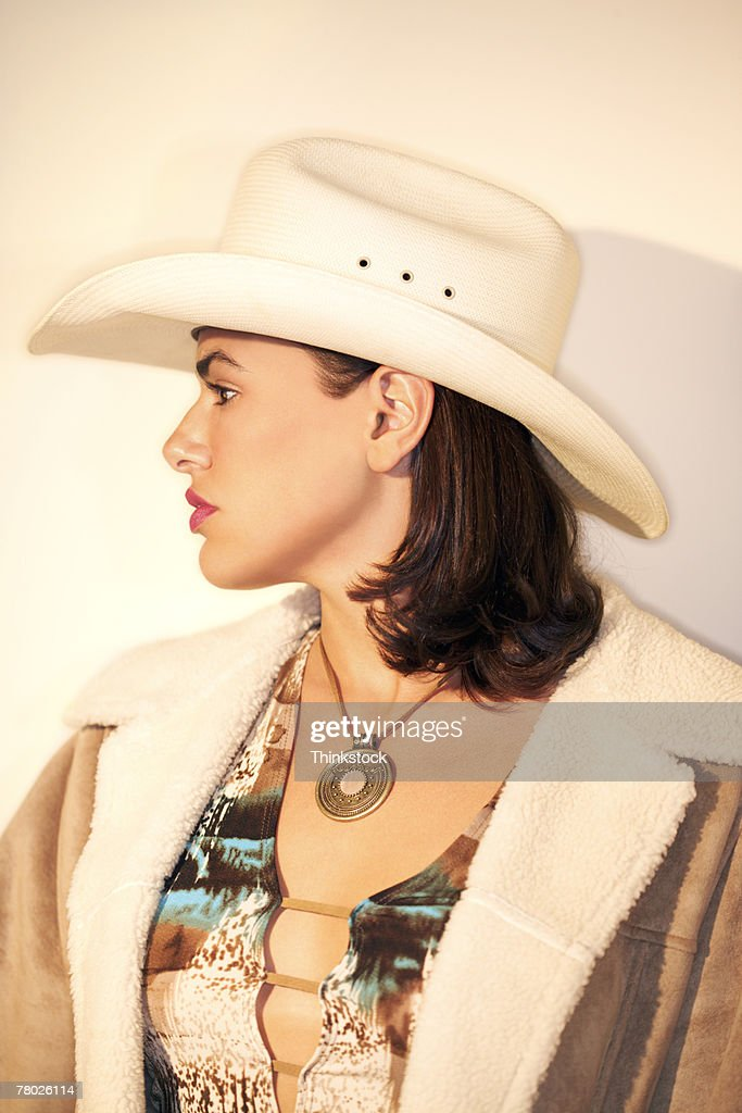 profile portrait of a cowgirl wearing a cowboy hat stock