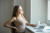 Profile portrait of a young woman, stretching, sitting feeling her back tired after working at laptop, small home office interior. Business concept photo, lifestyle