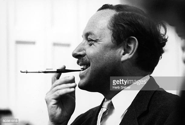 Profile portrait of playwright Tennessee Williams smoking with cigarette holder
