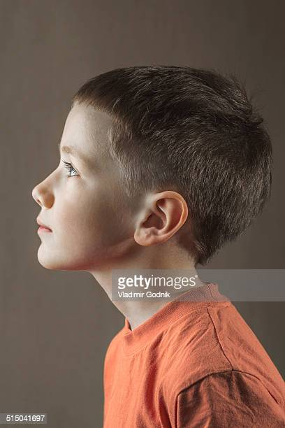 Profile shot of boy looking away over colored background