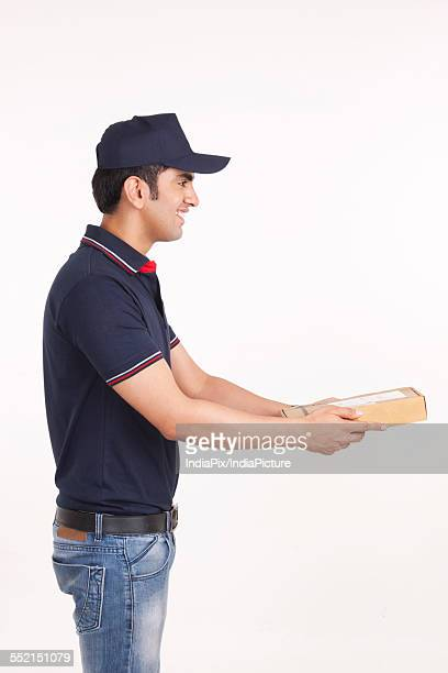 Profile shot of delivery man giving package against white background