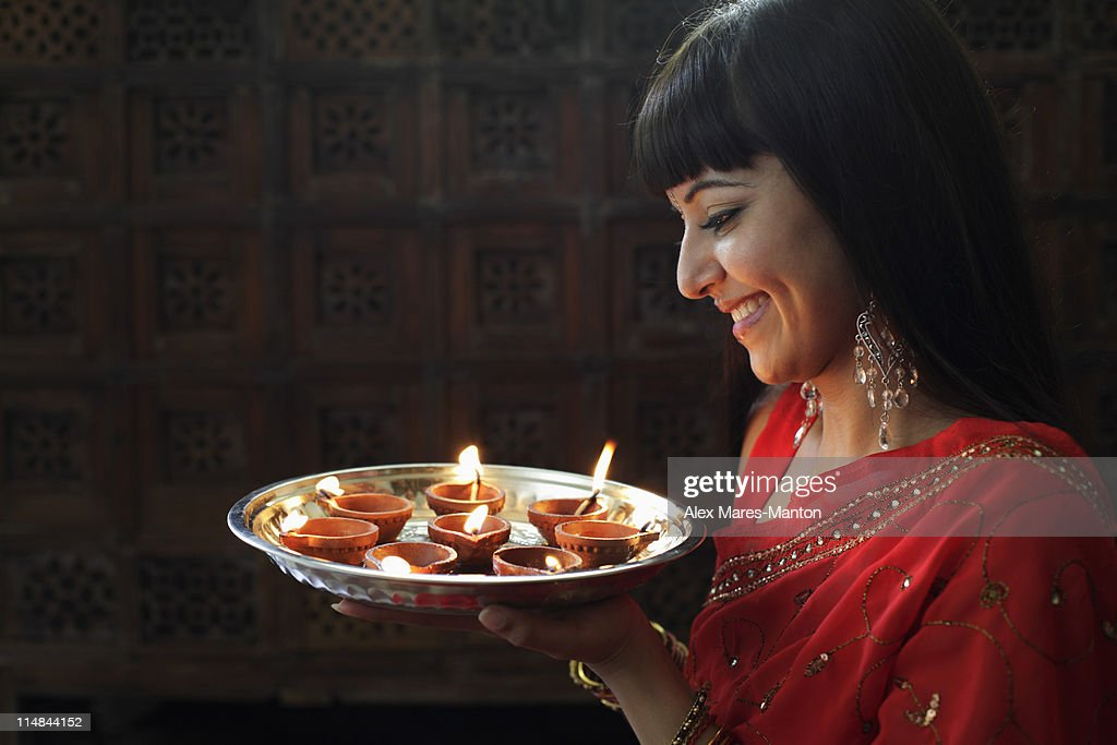 Profile shot of Indian woman holding a tray of lit oil lamps