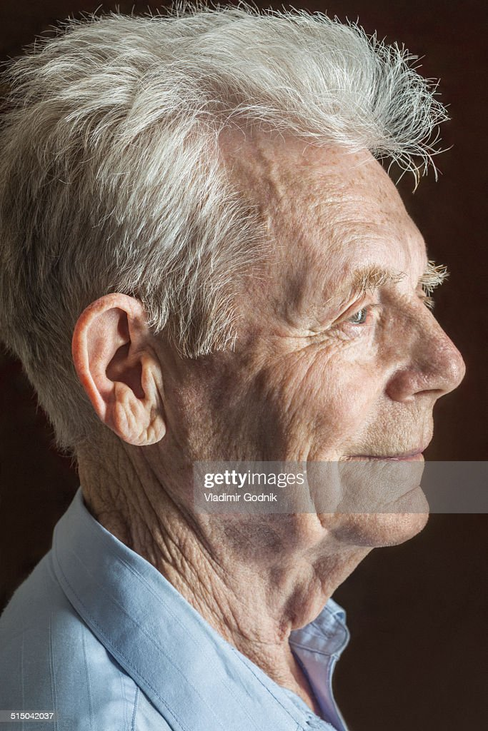 Profile shot of senior man over black background