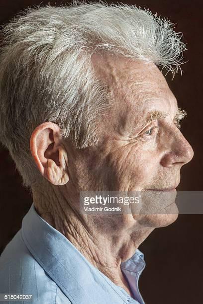 Profile shot of senior man over black background