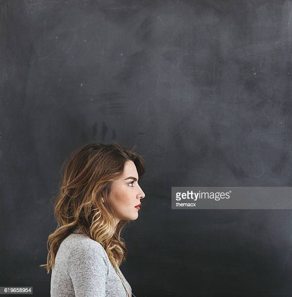 Profile shot of  young woman on blackboard