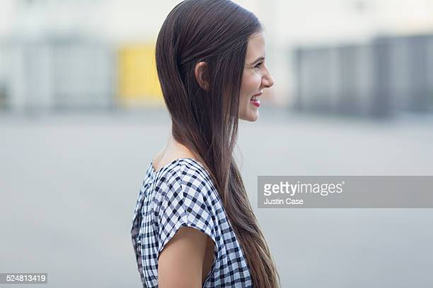 profile view of a woman laughing in the city