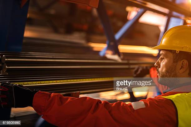Profile view of a worker measuring metal tubes in factory.
