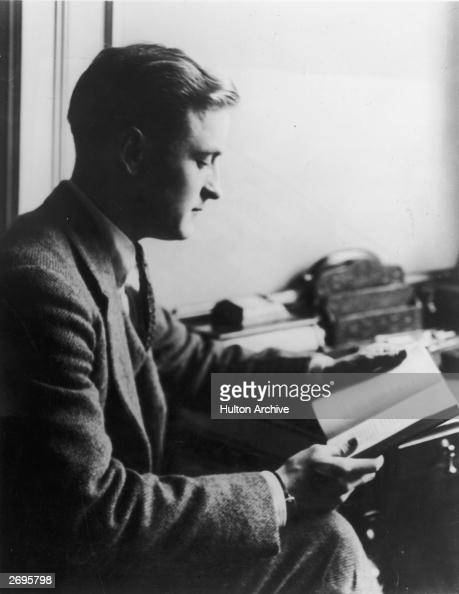 Profile view of American author F Scott Fitzgerald reading a book while sitting at a desk