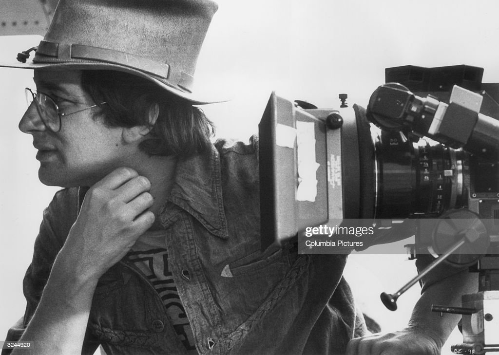 Profile view of American director Steven Spielberg working with a movie camera on the set of his film, 'Close Encounters of the Third Kind'.