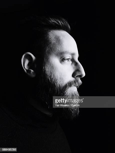 Profile View Of Bearded Mid Adult Man Against Black Background