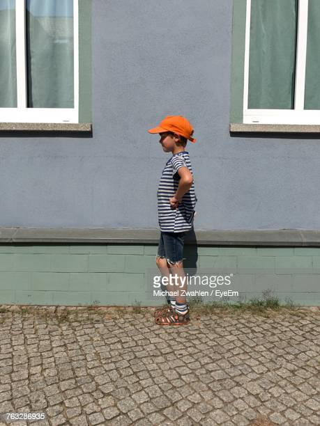 Profile View Of Boy Standing By Wall