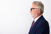 Profile view of happy senior bearded businessman smiling while wearing eyeglasses against white background horizontal shot