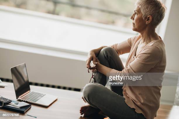 Profile view of pensive mature woman sitting on the table.