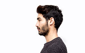 Profile view of serious young man over white background. Mug shot of young man isolated on white. Studio shot. Horizontal composition. Young man has got short black hair and beard.