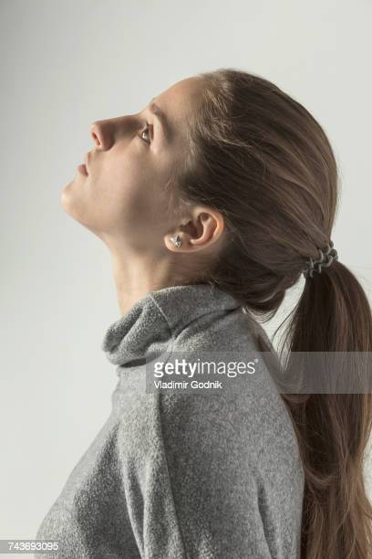 Profile view of teenage girl looking up against white background