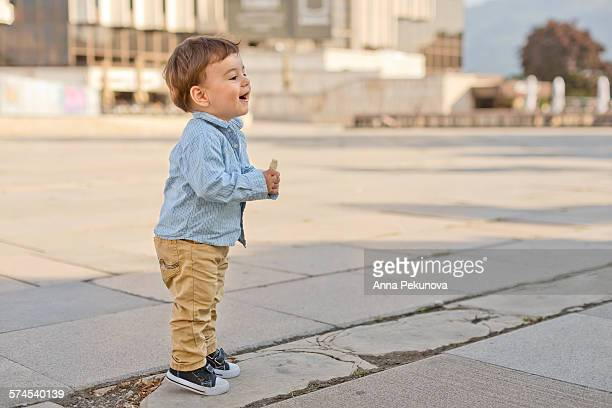 Profile view of toddler boy on tiptoe