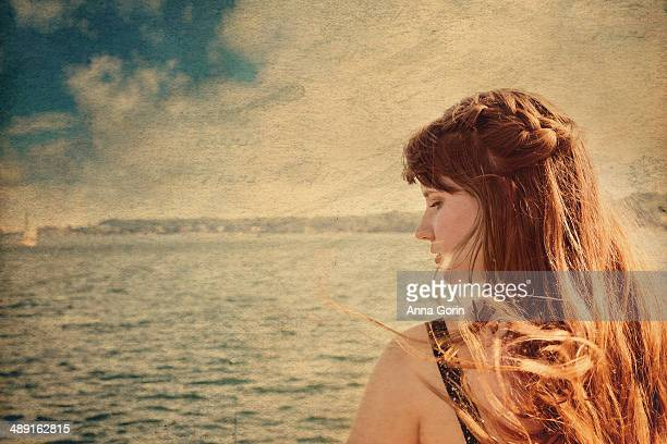 Profile view of woman with windswept hair by ocean