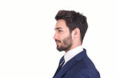 Profile view of young businessman in suit looking away over white background. There is smiling facial expression on his face. Side view, studio shot. Horizontal composition. Studio shot. Image taken w