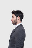 Profile view of young businessman in suit looking away over gray background. Vertical composition. Studio shot.