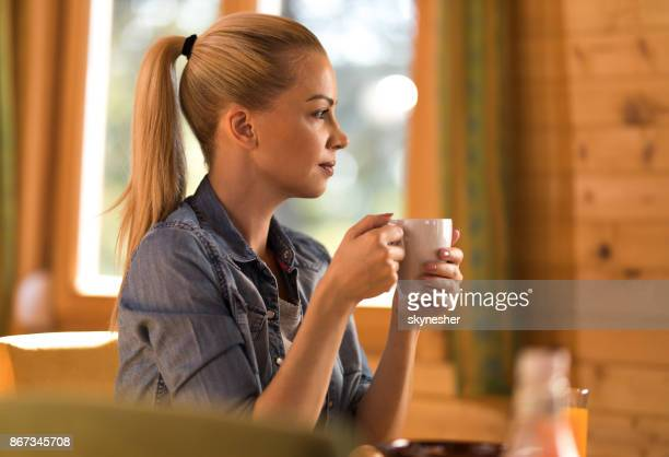 Profile view of young pensive woman having her coffee at home.