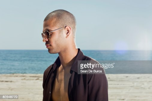 Profiled portrait of young man at beach : Stock Photo