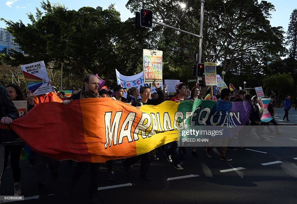 Pro-gay marriage supporters carry a rainbow banner and flags during a rally in Sydney on June 25, 2016. Hundreds of supporters of gay marriage marched through the streets of the central business district of Sydney for their rights. / AFP / SAEED