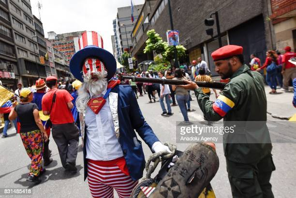A progovernment activist dressed up as a Venezuelan Bolivarian points a gun at a protester dressed up as Uncle Sam representing Unite States during a...
