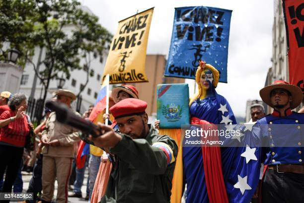 A progovernment activist dressed up as a Venezuelan Bolivarian points a gun during a rally to support Venezuelan President Nicolas Maduro and oppose...