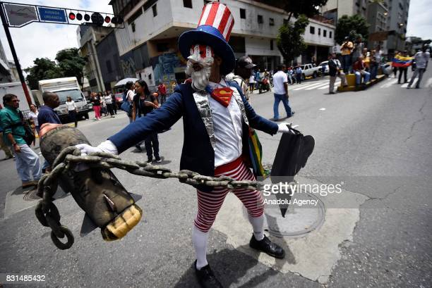 A progovernment activist dressed up as Uncle Sam representing Unite States performs during a rally to support Venezuelan President Nicolas Maduro and...