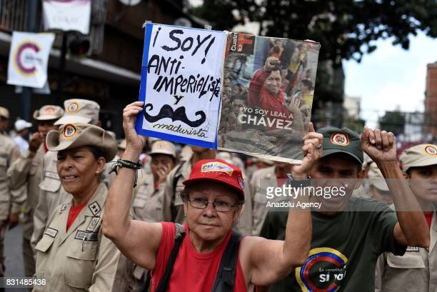 A progovernment activist holds a banner with an image of former Venezuelan President Hugo Chavez during a rally to support Venezuelan President...