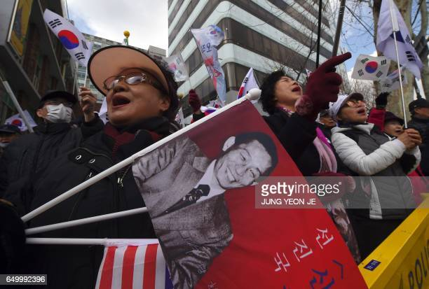 A progovernment activist holds a flag showing a portrait of former South Korean dictator Park ChungHee father of President Park GeunHye during a...