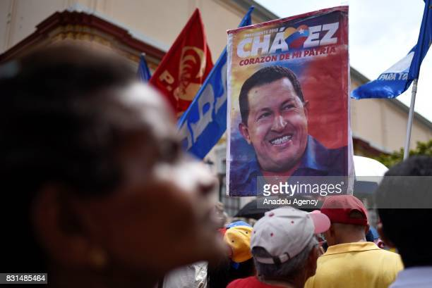 A progovernment activist holds an image of former Venezuelan President Hugo Chavez during a rally to support Venezuelan President Nicolas Maduro and...