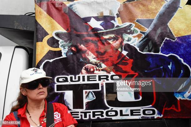 A progovernment activist stands in front of a banner of reading US' Uncle Sam with the phrase 'I want your Petroleum ' during a rally to support...